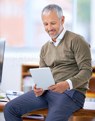 Buy stock photo A cropped shot of a happy businessman sitting on his desk with a tablet