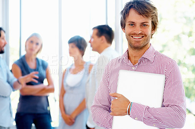 Buy stock photo Smiling business man holding laptop with team in blur background