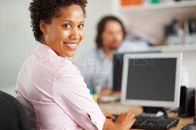 Buy stock photo Young African American business woman working on computer and smiling at you
