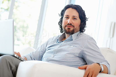 Buy stock photo Confident young business man sitting on couch with laptop