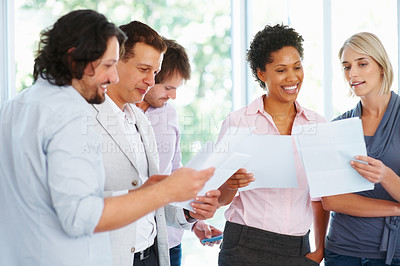 Buy stock photo Group of young professionals looking at business plan