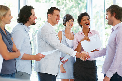 Buy stock photo Two business man shaking hands with his team in office