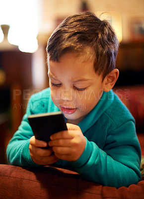 Buy stock photo Shot of a little boy playing with a cellphone