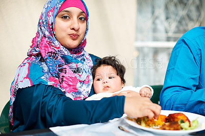 Buy stock photo Shot of a muslim mother and her little baby girl enjoying a meal together