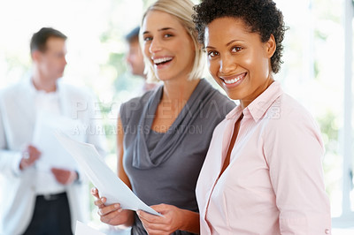 Buy stock photo Happy business women holding documents with team in background