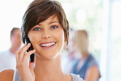 Buy stock photo Closeup of attractive woman using cell phone with team in background