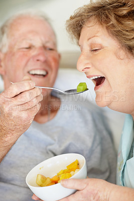 Buy stock photo Shot of playful senior couple feeding each other breakfast and laughing