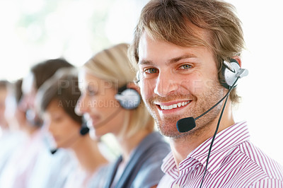 Buy stock photo Closeup of handsome young executive smiling with his team in row