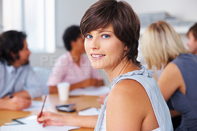 Buy stock photo Pretty woman taking notes while looking at you in meeting