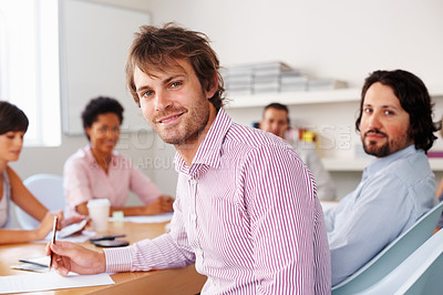 Buy stock photo Handsome man taking notes while looking at you in meeting