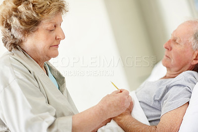 Buy stock photo Shot of a senor woman taking her sick husband's temperature