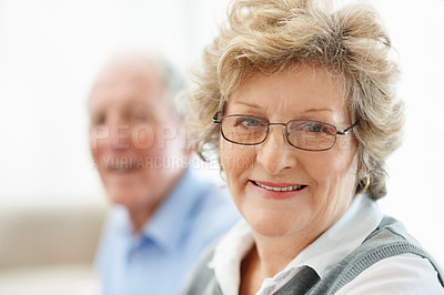 Buy stock photo Portrait of a senior woman sitting with her husband in the background