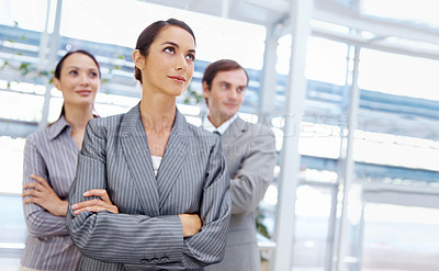 Buy stock photo Attractive businesswoman with her coworkers standing behind her while looking away