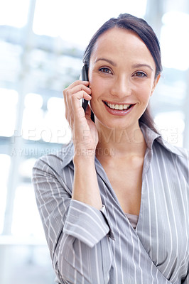 Buy stock photo Smiling young businesswoman taking a call on her mobile
