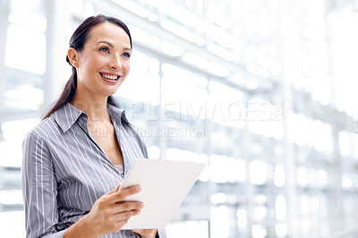 Buy stock photo Positive young businesswoman using her digital tablet with a smile - copyspace