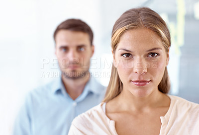 Buy stock photo Portrait of two serious-looking young business professionals standing in an office