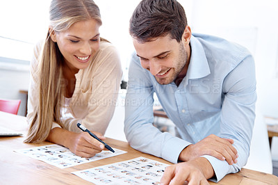 Buy stock photo Closeup shot of two young design professionals sitting at a table and editing photographs
