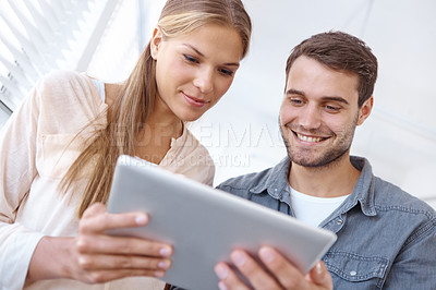 Buy stock photo Two young businesspeople looking at a digital tablet