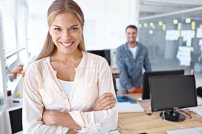 Buy stock photo Lovely young businesswoman smiling at the camera while her male colleague stands in the background