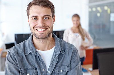 Buy stock photo Handsome young businessman smiling at the camera while his colleague stands behind him