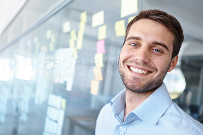 Buy stock photo Handsome young businessman leaning against a glass wall with post-it notes stuck to it - portrait