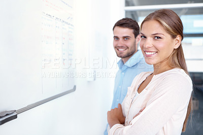 Buy stock photo Two businesspeople standing in front of a whiteboard and smiling at the camera - copyspace