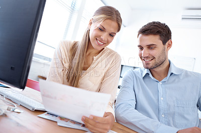 Buy stock photo Lovely young businesswoman showing a document to her colleague while sitting at a desk