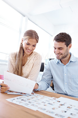 Buy stock photo Two co-workers looking through pages of photographs and making choices