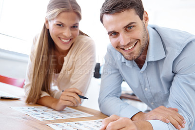 Buy stock photo Two co-workers looking at images and having a discussion