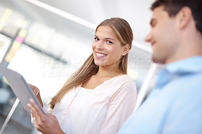 Buy stock photo Two young businesspeople holding a digital tablet while smiling at the camera - portrait