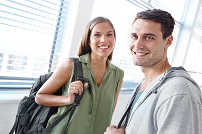 Buy stock photo Two young students standing in a hallway wearing backpacks
