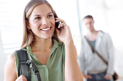 Buy stock photo Pretty young student talking on her cellphone with her male friend in the background
