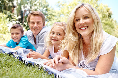 Buy stock photo A family of four lying on a picnic blanket together