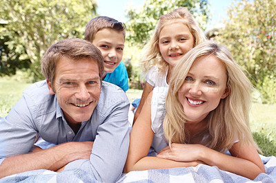 Buy stock photo A happy family of four lying on a picnic blanket together