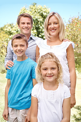 Buy stock photo Portrait of a loving family standing outdoors together on a bright day