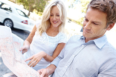 Buy stock photo A mature couple looking at a map while outdoors on a bright summer's day