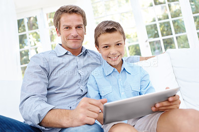 Buy stock photo A father and son using a digital tablet in the lounge together