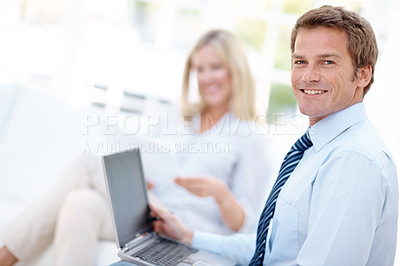Buy stock photo A handsome man working on his laptop with his wife blurred in the background
