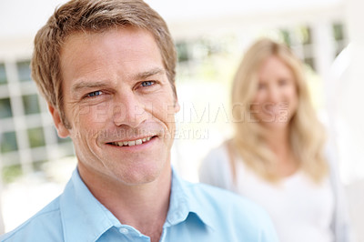 Buy stock photo A handsome mature man smiling with his wife blurred in the background