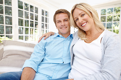 Buy stock photo Portrait of a mature couple sitting affectionately on the couch together
