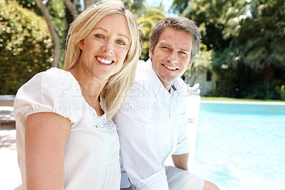 Buy stock photo A happy couple relaxing by the pool on a bright summer's day