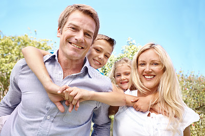 Buy stock photo Portrait of a happy family with the parents giving their children piggyback rides