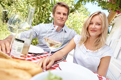 Buy stock photo Portrait of a smiling couple sitting outside drinking wine and eating a meal