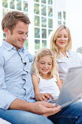 Buy stock photo A mother, father and daughter looking at a laptop
