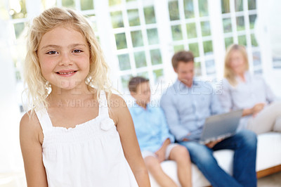 Buy stock photo Portrait of a smiling cute girl with her family blurred in the background looking at a laptop