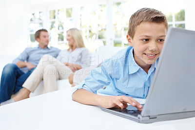Buy stock photo A smiling boy using a laptop with his parents in the background