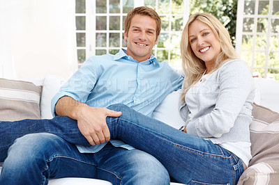 Buy stock photo Portrait of a smiling couple sitting comfortably with each other on the couch