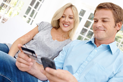 Buy stock photo A man sitting with his wife holding up a cell phone and a credit card