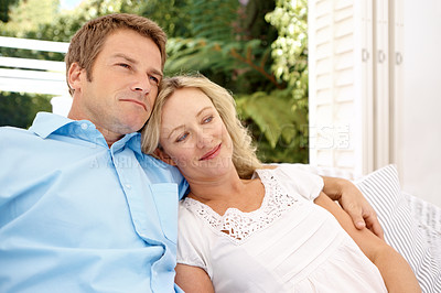 Buy stock photo A happy couple sitting on a chair outside looking content