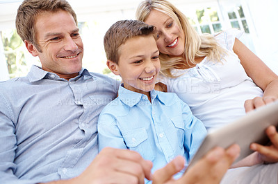 Buy stock photo Cute little boy using a digital tablet while sitting between his parents